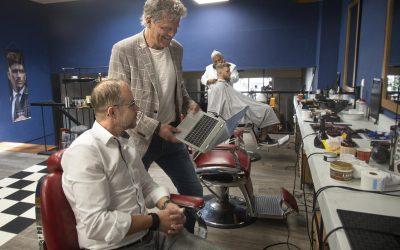 Eric van den Brandt (in stoel) krijgt in zijn kapperszaak ict-hulp van Bas Baalmans van de RUG. Foto: Jan Anninga